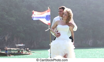 groom and bride smile against kayaks and longtail boats -...