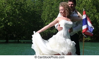european bride holds wedding dress tain looks at it against...