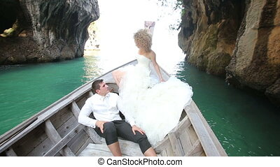 blonde bride and groom float in longtail boat among cliffs -...