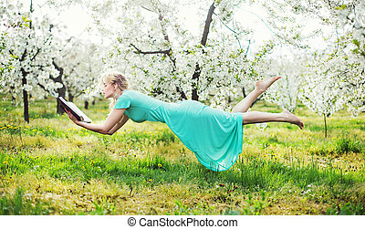 Adorable woman levitating during book reading - Adorable...
