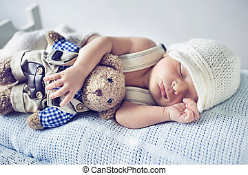 Newborn child sleeping with a teddy bear toy