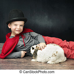 Little magician boy stroking a bunny - Little magician boy...