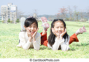 Cute happy children laying on grass outdoor