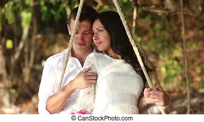 groom and bride roll on rope swing and join hands on beach -...