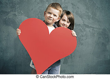 Boy and girl holding a toy heart - Boy and girl holding a...