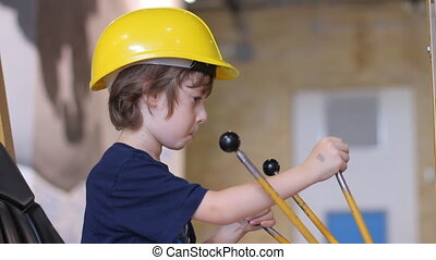 Boy in builder helmet sitting in excavator - Kid in yellow...