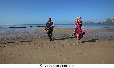 guitarist plays and blonde girl dances going from sea -...