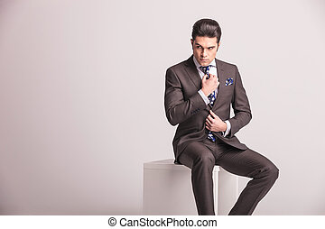 Attractive young business man fixing his tie