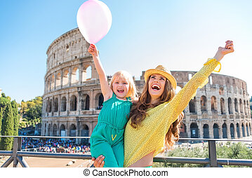 Cheering mother and daughter with pink balloon at Colosseum...