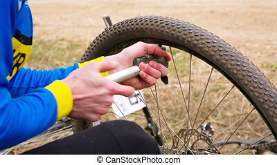 Contesting Cyclist Pumping In The Tire Of His Bike