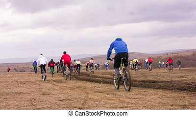 Group Of Young Bicycle Riders Moving In Field At Dull Day -...