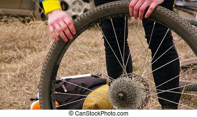 Professional Cyclist Repairing The Wheel Of His Bike -...