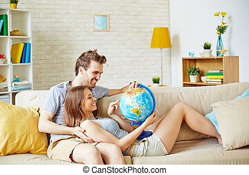 Travel lovers - Happy couple with globe choosing place for...