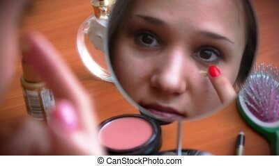 Young beautiful woman smears the face tone cream and smiling before a mirror