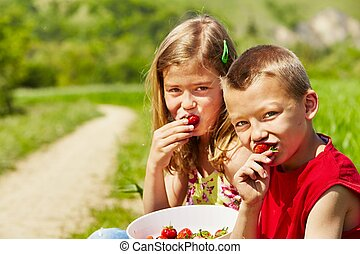 Fresh strawberries - Adorable siblings are eating fresh...