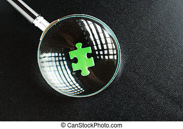 Green puzzles and magnifying glass on a black leather...