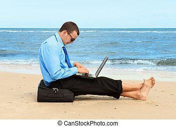 businessman on the beach - young businessman working with...