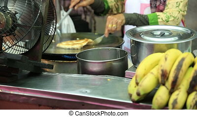 vendor fries up delicious roti - Thai street vendor fries up...
