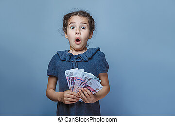 teen girl of European appearance holds five denominations of...