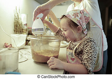 Mother and daughter preparing dough in the kitchen
