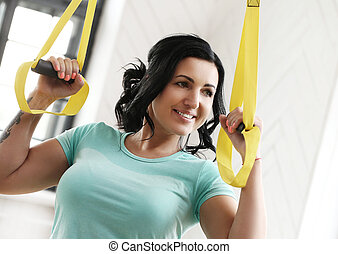 Girl at gym - TRX. Beautiful woman at gym