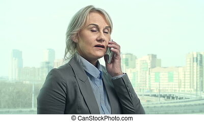 Phone Call - Front view of business-like woman standing at...