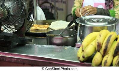 vendor fries up delicious roti - Thai street vendor fries up...