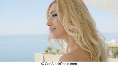Blond Woman Admiring View from Ocean Front Balcony - Close...