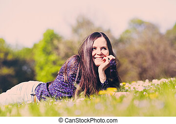 Girl lying down on grass - Retro toned portrait of joyful...