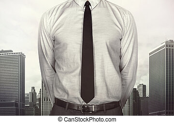 Businessman on cityscape background - Businessman with tie...