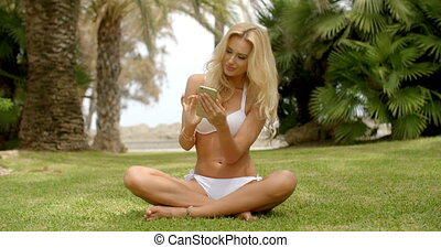 Woman in Bikini Sitting on Grass with Cell Phone - Full...