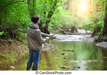 Fisherman with fly-fishing on mountain river Spring time