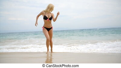 Woman in Bikini Playing in Beach Surf