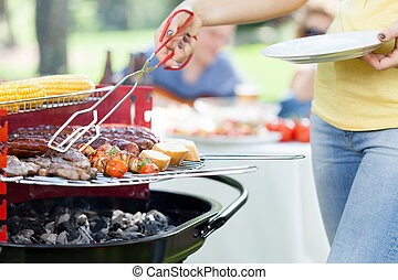 Woman serving grilled steak on garden party