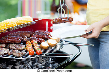 Woman dishing out grilled sausage - Closeup of woman dishing...