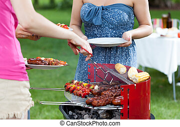 Host serving meals on barbecue party - Host serving grilled...