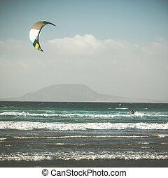 kitesurfing in ocean near mountain