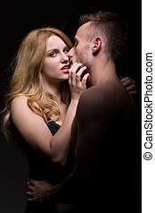 Passionate sexy couple posing on black background