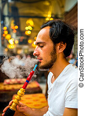 Man smoking turkish hookah in the cafe with coloful lamps on...