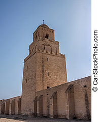 Tower of the Great Mosque in Kairouan against a blue sky. A...
