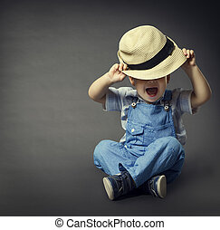 Baby Boy in Fashion Jeans, Hat Covered Eyes. Child Beauty...