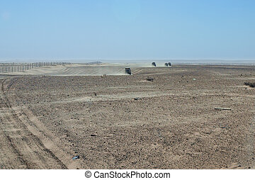 Convoy of 4x4 vehicle drive a dusty desert track in Tunisa -...