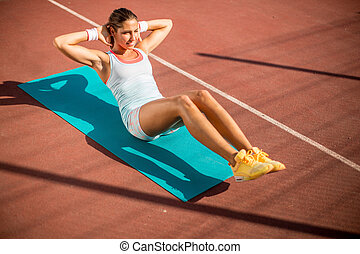 Young woman taking exercise outdoors