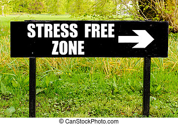 STRESS FREE ZONE written on directional black metal sign...