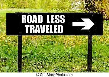 ROAD LESS TRAVELED written on directional black metal sign...