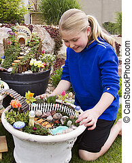 Young girl helping to make fairy garden in a flower pot...