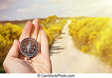 Compass in the hand against rural road