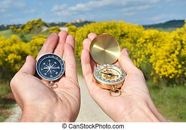 Man and woman holding compasses against rural road