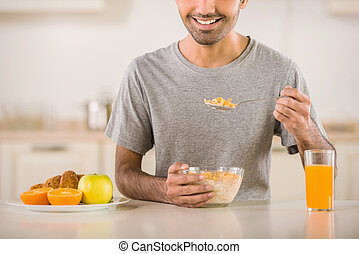 Breakfast - Young man in grey t-shirt eating corn flakes...