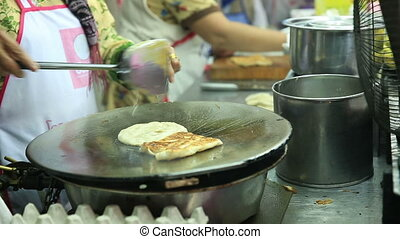 Thai street vendor fries up roti - Thai street vendor fries...